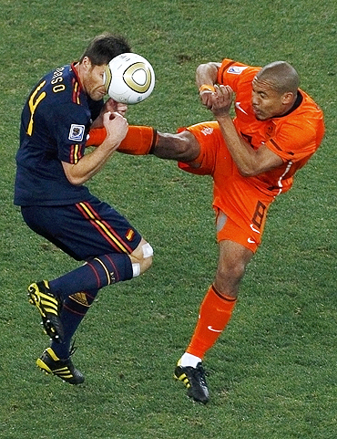 Spain's Xabi Alonso gets a boot in his chest as he is challenged by Dutch Nigel de Jong