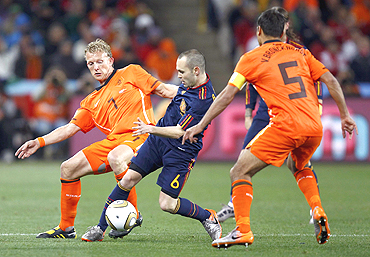 Netherlands' Dirk Kuyt and Spain's Iniesta (centre) vie for possession