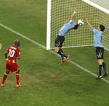 Uruguayan striker Luis Suarez (right) stops a goal with his hand