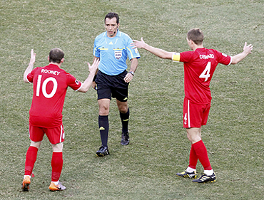 Wayne Rooney and Steven Gerrard argue with Larrionda