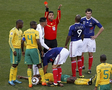 Referee Ruiz gestures after showing the red card to France's Gourcuff for a foul on South Africa's Sibaya