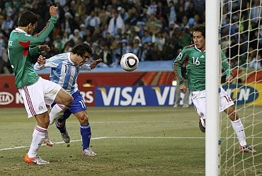 Carlos Tevez scores in a match against Mexico