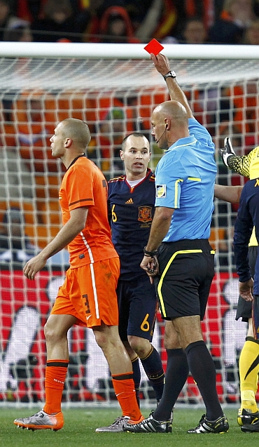 Referee Howard Webb gives a red card to John Heitinga