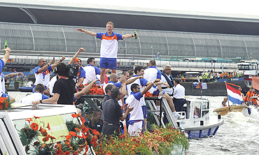 Dutch players acknowledge fans during a canal parade in Amsterdam