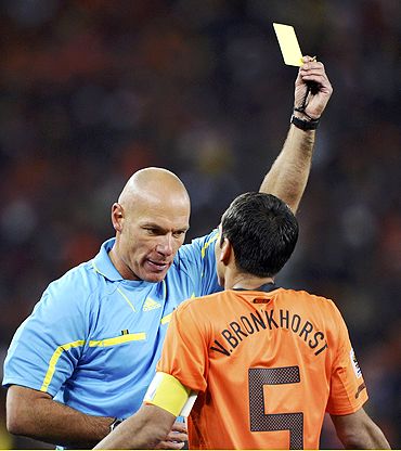 Dutch captain Giovanni van Bronckhorst is shown the yellow card by referee Howard Webb