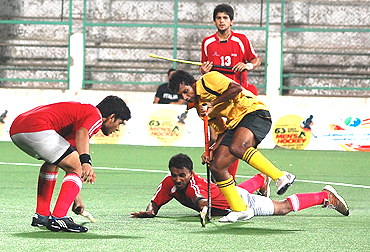 A player from Tamil is challenged by Delhi players