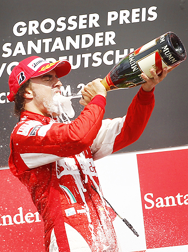 Ferrari's Fernando Alonso sprays champagne after winning the German Grand Prix on Sunday