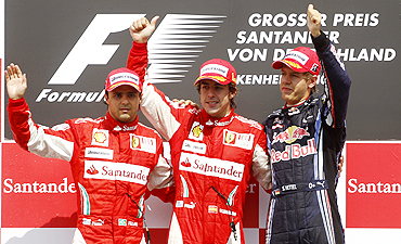 Ferrari'S Fernando Alonso (centre) celebrates on the podium with team-mate Filipe Massa and Red Bull's Sebastian Vettel
