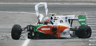 Force India Formula One driver Vitantonio Liuzzi removes a part of his car to get out after crashing in the qualifying session for the German F1 Grand Prix on Saturday