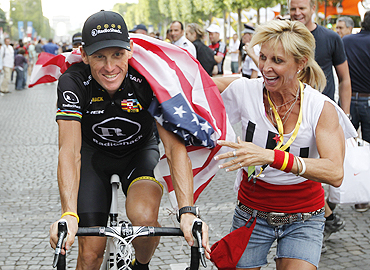 A fan drapes the US flag around Armstrong during the final parade of Tour de France on the Champs Elysees