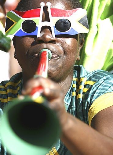 A soccer fan blows a vuvuzela