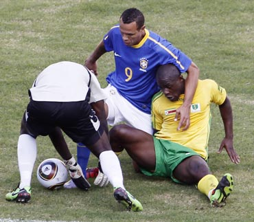 Brazil's Luis Fabiano fights for the ball against Zimbabwe's Nengomasha during their friendly match