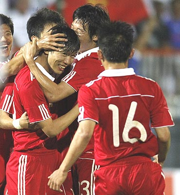 China's Deng Zhuoxiang (centre) celebrates with team-mates after scoring against France during their friendly tie at Michel Volnay stadium