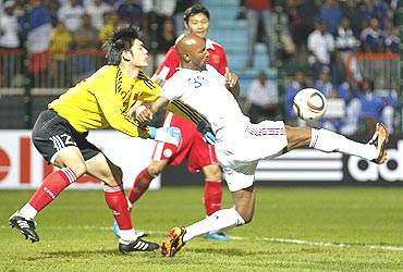 France's Nicolas Anelka (right) is challenged by China's goalkeeper Zeng Cheng (left) during their friendly tie