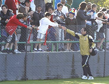 Japan's head coach Takeshi Okada greets spectators in George
