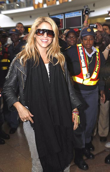 Colombian singer Shakira is escorted by police as she arrives at the Oliver Tambo International Airport in Johannesburg on Monday