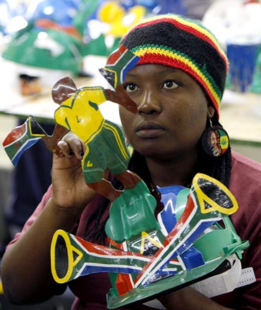 A worker paints a makarapa fan helmet at a factory in Wyneburg