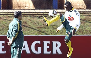 South Africa's Teko Modise controls the ball during a training session as coach Carlos Alberto Parreira (left) looks on