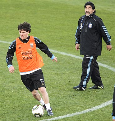 Argentina's Lionel Messi trains as Maradona looks on