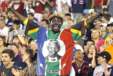 A fan wearing the colors of South Africa and a portrait of Nelson Mandela cheers during a World Cup warm-up match