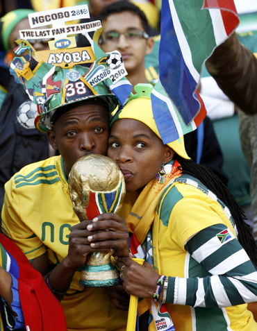 -Soccer fans kiss a replica of the World Cup trophy during the opening ceremony of the 2010 World Cup