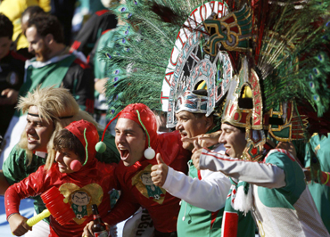Mexican fans in costumes cheer during the opening ceremony before the 2010 World Cup opening match