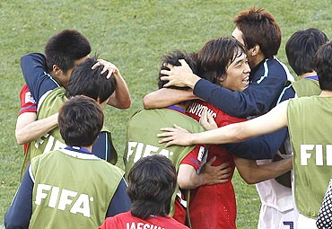 South Korean players celebrate after winning the match against Greece