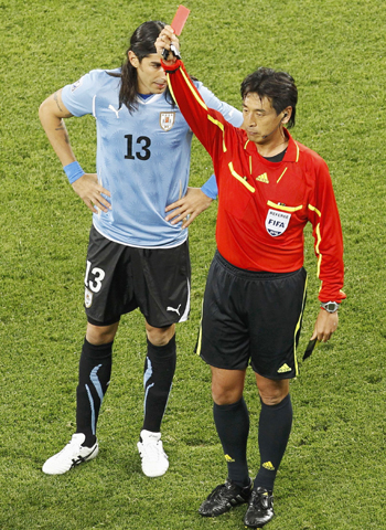 Referee Nishimura flashes the red card at Nicolas Lodeiro as Uruguay's Abreu looks