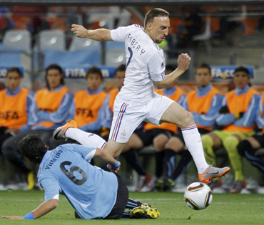 France's Franck Ribery avoids a tackle by Uruguay's Mauricio Victorino