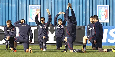 Italian players stretch during a training session