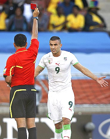Referee Carlos Alberto Batres of Guatemala shows the red card to Algeria's Abdelkader Ghezzal