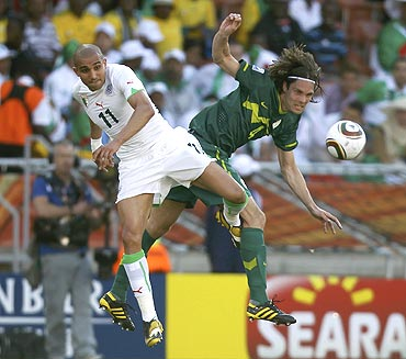 Algeria's Rafik Djebbour (left) Slovenia's Marko Suler are involved in an aerial duel