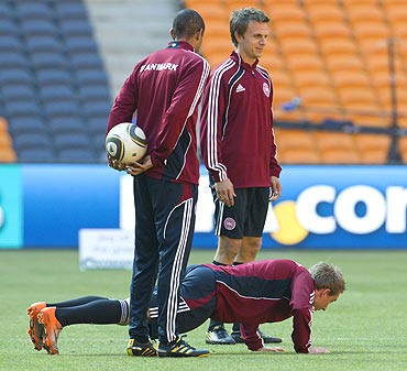 Denmark's Christian Eriksen does push-ups while team-mates Jesper Gronkjaer (right) and Simon Poulsen watch at a training session