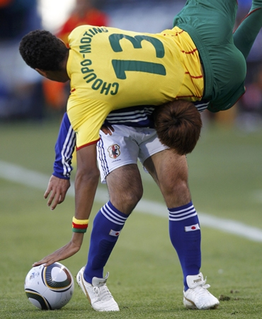 Japan's Yuichi Komano is challenged by Cameroon's Eric Choupo-Moting