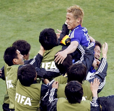 Honda celebrates with team mates after scoring