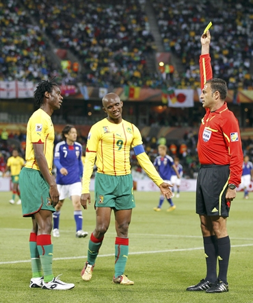 Cameroon's Nicolas Nkoulou (L) receives a yellow card from referee Olegario Benquerenca (R) of Portugal as his captain Samuel Eto'o watches