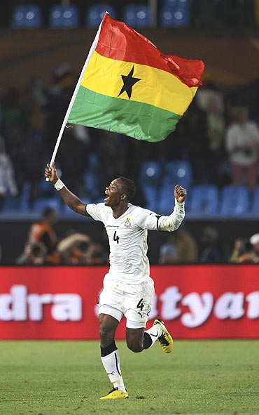 Ghana's John Pantsil celebrates with his national flag after beating Serbia