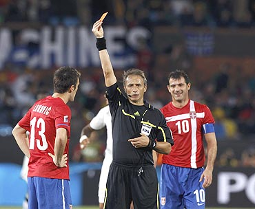 Serbia's Aleksandar Lukovic receives a red card from referee Hector Baldassi of Argentina