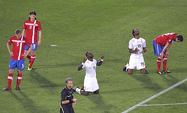 Ghana's John Mensah and Isaac Vorsah thank the Almighty after defeating Serbia