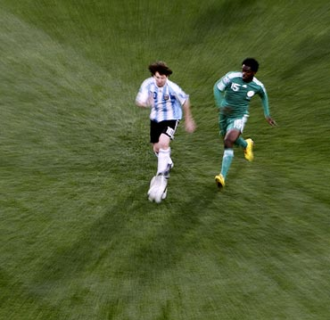 Lionel Messi gets the ball past Nigeria's Haruna Lukman