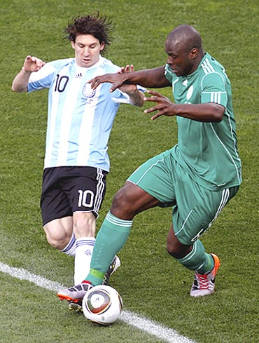 Argentina's Lionel Messi and Nigeria's Danny Shittu vie for possession