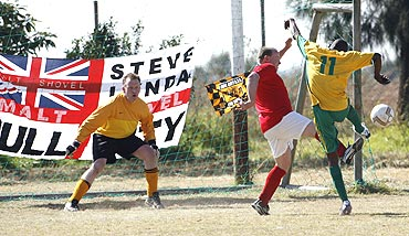 South African inmate Tshepiso Mofokeng fights for possession as keeper Alex Sheilds (left) watches