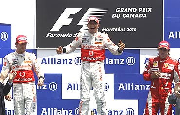 McLaren's Lewis Hamilton (centre) alongside second-placed team-mate, Jenson Button (2nd from left) and third-placed Fernando Alonso of Ferrari on the podium