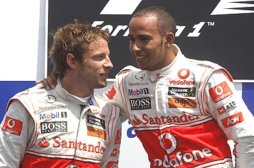 McLaren's Lewis Hamilton (right) celebrates with team-mate Jenson Button on the podium after winning the Canadian GP