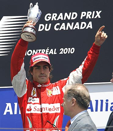 Ferrari Formula One driver Fernando Alonso holds up his third-place trophy