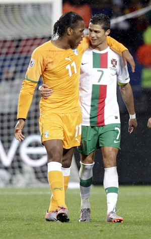 Ivory Coast's Didier Drogba walks with Portugal's Cristiano Ronaldo