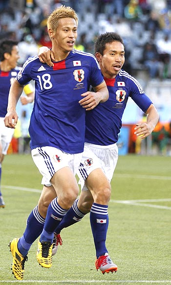 Keisuke Honda (left) celebrates with a team-mate after scoring against Cameroon