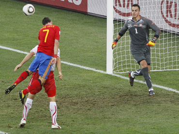 Spain's David Villa jumps for the ball next to Switzerland's Reto Ziegler as goalkeeper Diego Benaglio looks on