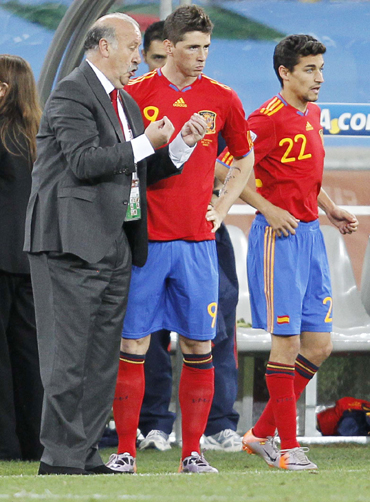 Spain's Torres and Navas listen to coach Del Bosque before coming on during the 2010 World Cup Group H match against Switzerland