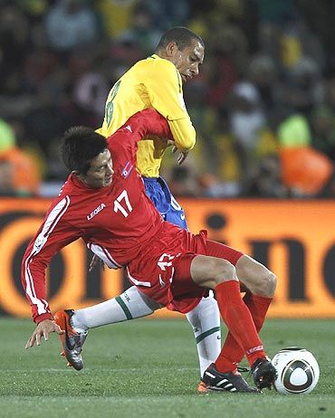 North Korea's An Yong-hak (left) vies for the ball with Brazil's Gilberto Silva